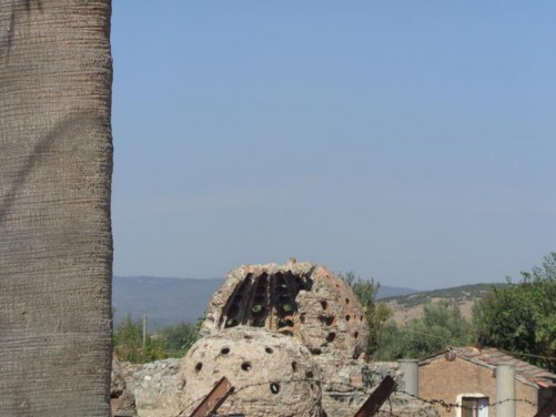 Ruins of a hammam (bathhouse) south of the Isa Bey Mosque. Two stone domes, one partly collapsed, in view.