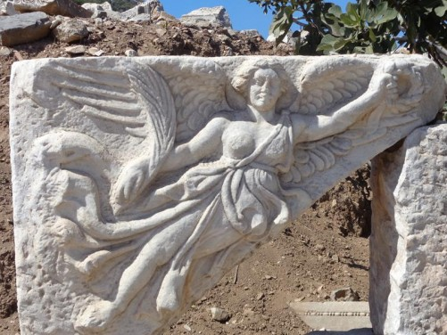 Carving of the winged Roman goddess Nike on a stone block.