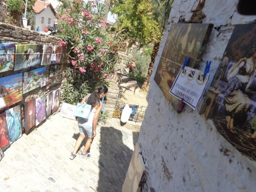 Heading down a winding narrow street in Sirince village. Paintings for sale of the walls.