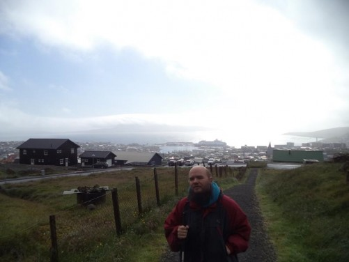View down a sloping gravel path with the buildings of Tórshavn, as well as the harbour, below. The glow of the rising sun reflecting through cloud on to the sea beyond. Tony in the foreground.