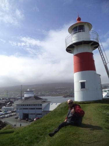 Tony sitting on top of a grass covered hill overlooking the harbour. A small red and white painted lighthouse standing alongside.