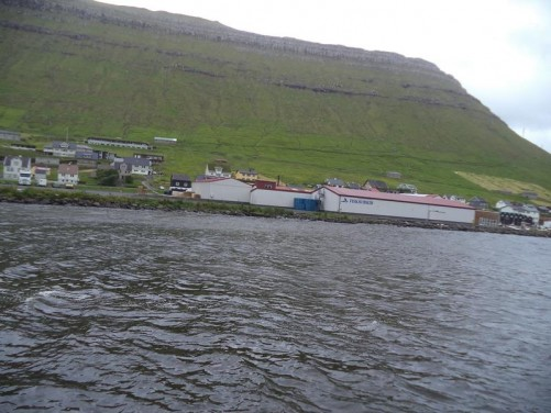 View of Norðragøta, a small town on Eysturoy Island. Eysturoy is the second largest of the Faroe Islands, located east of Streymoy. The town sits in a fjord. Scattered buildings in the foreground with a steep slope rising up to 400 metres behind.