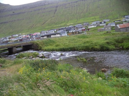 Another view of Norðragøta. A wide stream flowing in front amongst long grass.