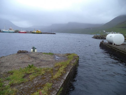 The harbour in Fuglafjørður. Mountains in the distance partly obscured by cloud.