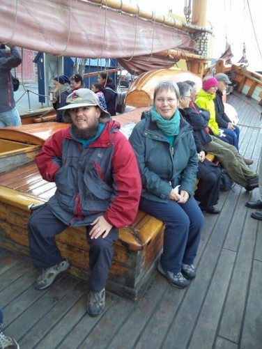 Tony on-board a traditional wooden fishing schooner, built in Norway in the late 19th century. Other passengers sitting around the deck.