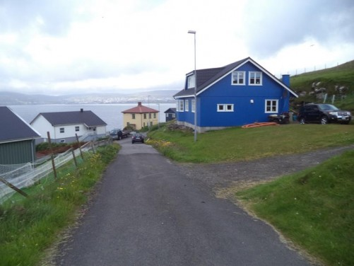 Looking down a street in Nólsoy village. A cluster of houses in front and beyond the three mile wide channel separating Nólsoy from the main island of Streymoy. Tórshavn is just visible away in the far distance lit by the sun.