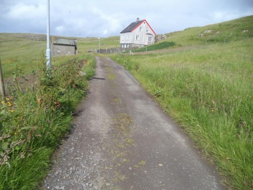 Continuing uphill along the narrow road. A single isolated house approaching amongst the grassy scenery.