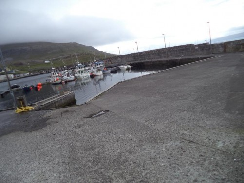 The harbour in Nólsoy village. A handful of small boats in front.