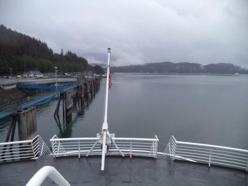 Again looking from the ferry's stern. An American flag waving immediately below. Harbour side walkways alongside.