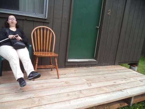 Tatiana relaxing outside a wooden cabin at Bear Creek Cabins, Haines, Alaska. Afternoon of 6th June.
