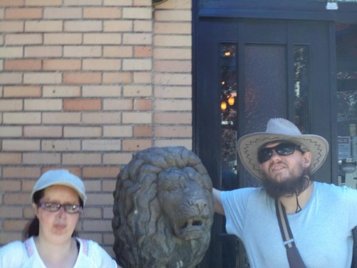 Tony and Tatiana next to a stone lion's head on a street in central Seattle.