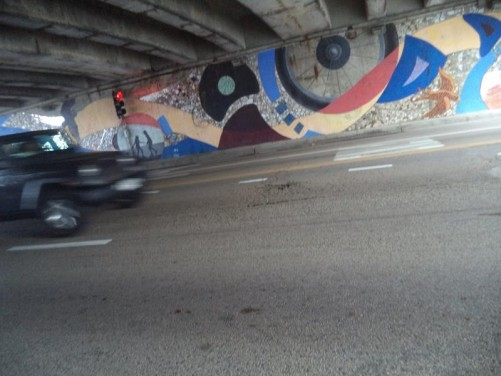 A main road passing through a concrete underpass. The wall opposite decorated with a large mural, depicting things including a bird and bike wheel.