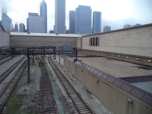 View from a railway bridge towards skyscrapers, including the 346 metre (1,136 foot) Aon Center completed in 1974 (its top out of view). The building in the foreground is the Art Institute of Chicago.