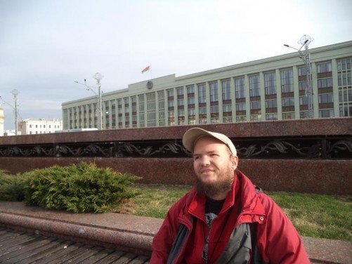 Tony sitting on a bench in Independence Square. This large rectangular square is located in central Minsk. In the background, the large Minsk City Council building, completed in 1984.