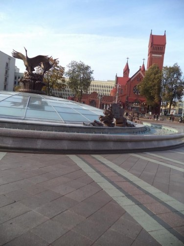 Still in Independence Square. In the foreground, the central fountain with a bronze sculpture of birds in the centre of its glass dome. Beyond, a view of the red brick Church of Saints Simon and Helena (also known as the Red Church). Built between 1905 and 1910. It was named and consecrated in memory of prominent business man Edward Woynillowicz's two deceased children, Szymon and Helena. It is Roman Catholic in affiliation.