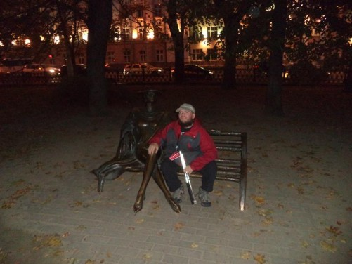 Tony next to a bronze statue of a woman sitting on a bench. Taken in Mikhailovsky Park during the evening.