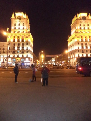 The Minsk Gates, two 11-storey buildings resembling castle towers. One has a large clock, its face is the largest in Belarus. At Station Square, in front of Minsk train station in the evening. Tony in front.