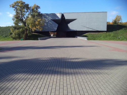 Main entrance to Brest Fortress passing under a huge concrete block with a five-pointed star cut into it.