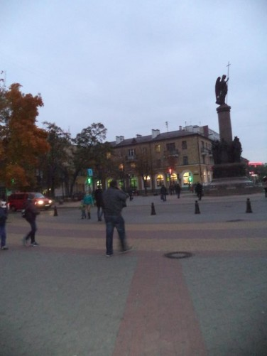 The Millennium Monument at the intersection of Sovietskaya and Gogol streets in the early evening twilight. It was designed by Belarusian architect Alexei Andreyuk and was constructed between 2009 and 2011. A bronze sculpture of the Angel of Mercy with a cross stands on top of a 15.1 metre high granite column.