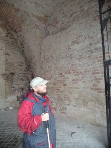 Tony inside the outer entrance to Old Grodno Castle (also known as the Grodno Upper Castle and Bathory's Castle). Next to an arching brick wall.