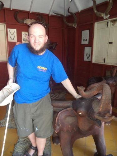 Tony touching a wooden chair designed in the form of an African elephant.