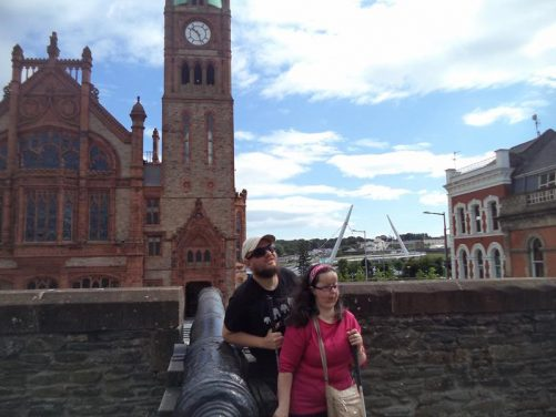 Tony and Tatiana next to an old canon on the city walls. Beyond is the imposing red-brick late-Victorian Guildhall, crowned by a copper dome.