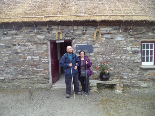 Tony and Tatiana in the doorway of a small stone cottage with a thatched roof.