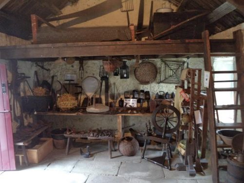 Inside another cottage looking at a display of agricultural and craft tools.