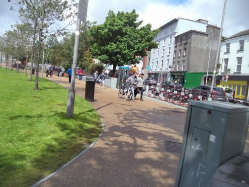 Eyre Square, which contains John F. Kennedy Park, located at Galway's centre. A tree-lined path with a road and buildings to one side.