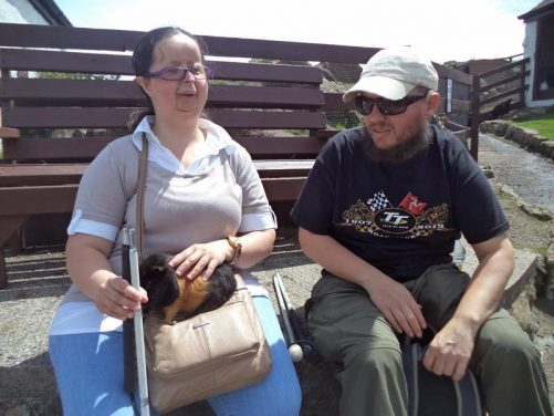 Tony and Tatiana sitting down. Tatiana has a guinea pig on her lap.