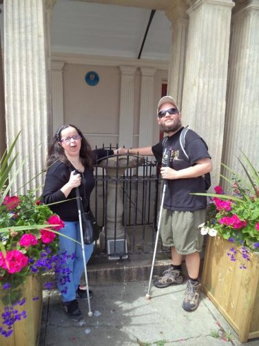 Tony and Tatiana at Queen Anne's Walk. This was originally a meeting place for the town's merchants completed in 1713. The Tome Stone can be seen protected by railings behind. It is a low stone circular bargaining table where merchants sealed deals.