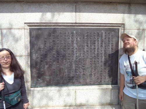 Tony and Tatiana in front of a memorial plaque.