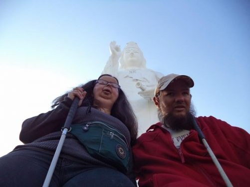 Tony and Tatiana at the foot of a statue at Tall Buddha Temple.