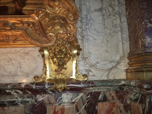 Ornate wall decoration including a golden lion's head inside the Hercules Salon at the Palace of Versailles.