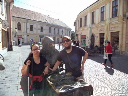 Tony, Tatiana with the bronze statue of Aunt Kati pushing her cart of local produce in the old market square. Rubbing her nose, apparently, brings a person luck!
