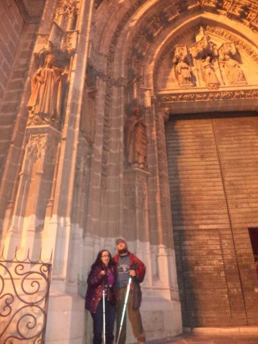 Tony and Tatiana outside the massive Door of Baptism on the west façade of Seville Cathedral. The doorway was built in the 15th century and decorated with carving depicting the baptism of Jesus.
