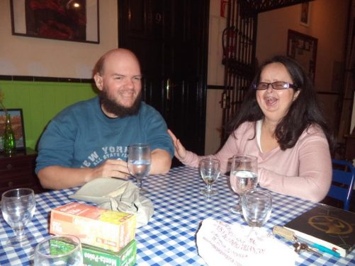 Tatiana and Tony sitting at a table inside Traveler's Inn, the hostel where they stayed. Calle Augusto Plasencia 5, Plaza de la Alfala, Seville (Sevilla), Andalusia, Spain.