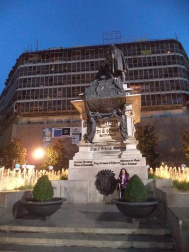 Tatiana in front of a bronze statue of Queen Isabel granting Columbus permission to set off on his voyage of discovery. The statue stands on a high rectangular stone base and is surrounded on three sides by fountains. It is located in Plaza Isabel La Catolica and was built in 1892. Photo taken during the evening.