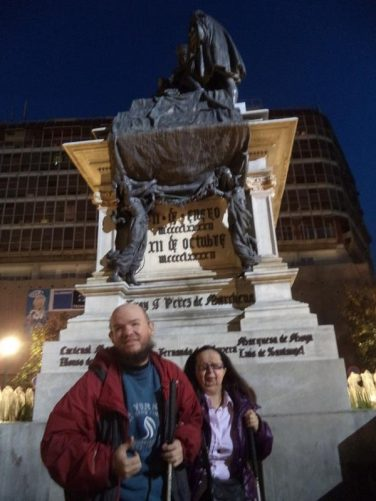 Tony and Tatiana next to the statue in Plaza Isabel La Catolica.
