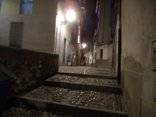 A deserted dimly lit side street in Granada's historic Albayzín district.
