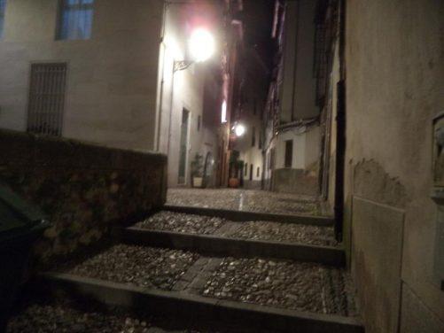 A deserted dimly lit side street in Granada's historic Albayzín district.