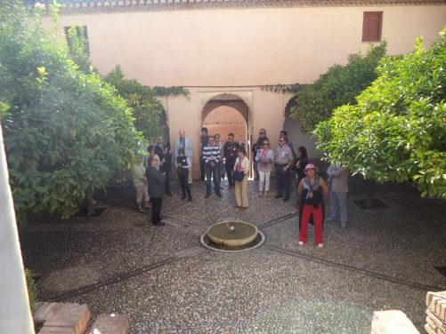 A small shaded courtyard within the Generalife palace. A group of visitors being led on a tour in front.