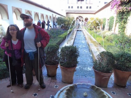 Tony and Tatiana at one end of the Patio de la Acequia. Located at the centre of the Generalife palace buildings, this courtyard contains a long rectangular pool with jets of water arching over the top. There are flower beds running along the sides.