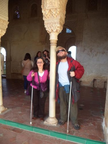 Tatiana and Tony either side of an elaborately carved stone pillar at the Generalife. The palace's architecture is Moorish Islamic in style.
