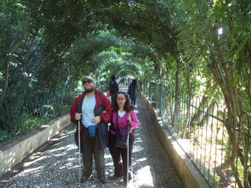 Tony and Tatiana standing at the end of a long straight path shaded by trees formed into an arch.