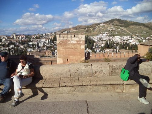 People sitting on stone benches with the Alhambra's red stone walls in view beyond. A crenellated tower in the centre.