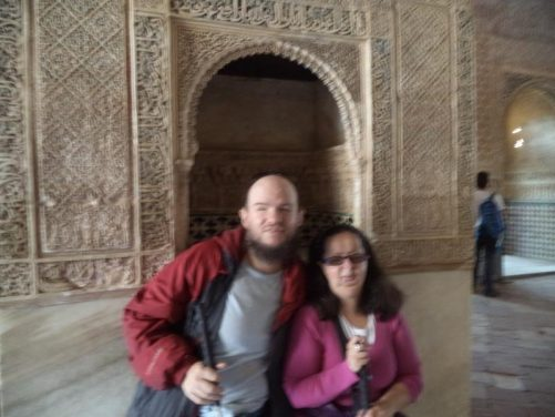 Tony and Tatiana in a room within the Nasrid Palace. Intricate moulded plaster work on the wall and alcove behind. The decoration includes complex geometric patterns and Islamic script.