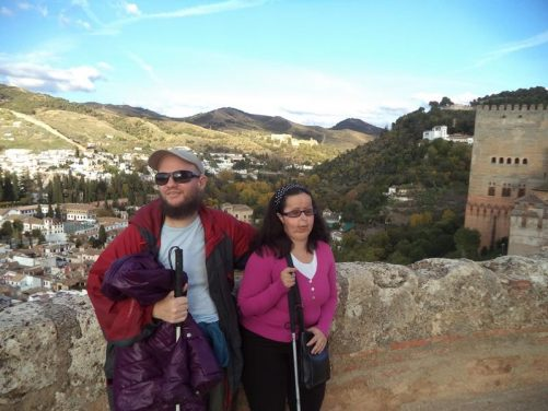 Tony and Tatiana on the walls of the Alcazaba with a view of the city below. Further along the walls, the Comares Tower can be seen. This tower is part of the Nasrid Palace. It is the highest of the Alhambra's towers at 45 metres in height.