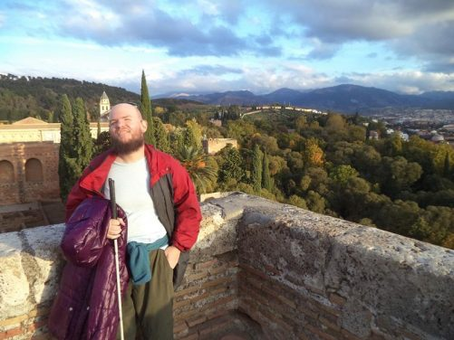 Tony by the Alcazaba's outer wall. Wooded landscape below with the Sierra Nevada mountains rising up on the horizon.