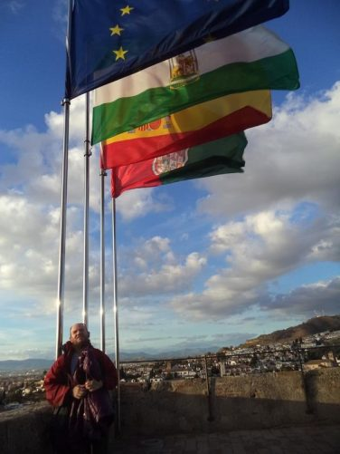 Tony in front of four flag poles. They are flying the flags of the EU, Andalusia, Spain and Granada.